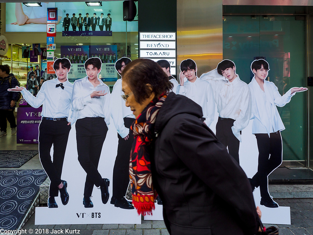 """14 OCTOBER 2018 - SEOUL, SOUTH KOREA: A woman walks past a cardboard figure of the K-Pop boy band """"BTS"""" in front of a cosmetics shop in the neighborhood around Myeongdong Street between the Cathedral and City Hall in Seoul. It's a high end shopping, dining and entertainment district, popular with tourists and wealthy South Koreans.      PHOTO BY JACK KURTZ"""