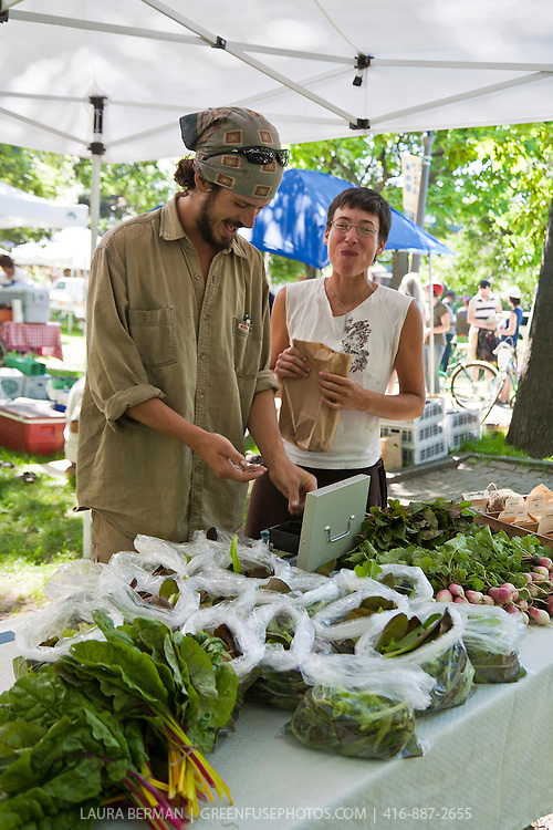 Hanna and Eric of Matchbox Garden and Seed Co. selling their organically grown produce at a farmers market in Toronto