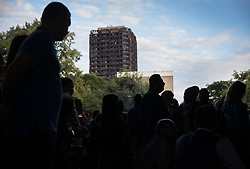 © Licensed to London News Pictures. 14/08/2017. London, UK. People stand under the A40 flyover - in sight of the remains of Grenfell tower after marching in silence to remember the victims of the fire.  The silent march takes place every month to remember the 80 residents of the 24 storey tower block that died in the tragedy on June 12, 2017 in Kensington. Photo credit: Peter Macdiarmid/LNP