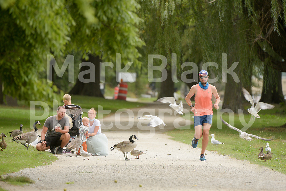 Jogger people feeding birds in Lincoln Park in Chicago on Thursday, Sept. 3, 2020. Photo by Mark Black