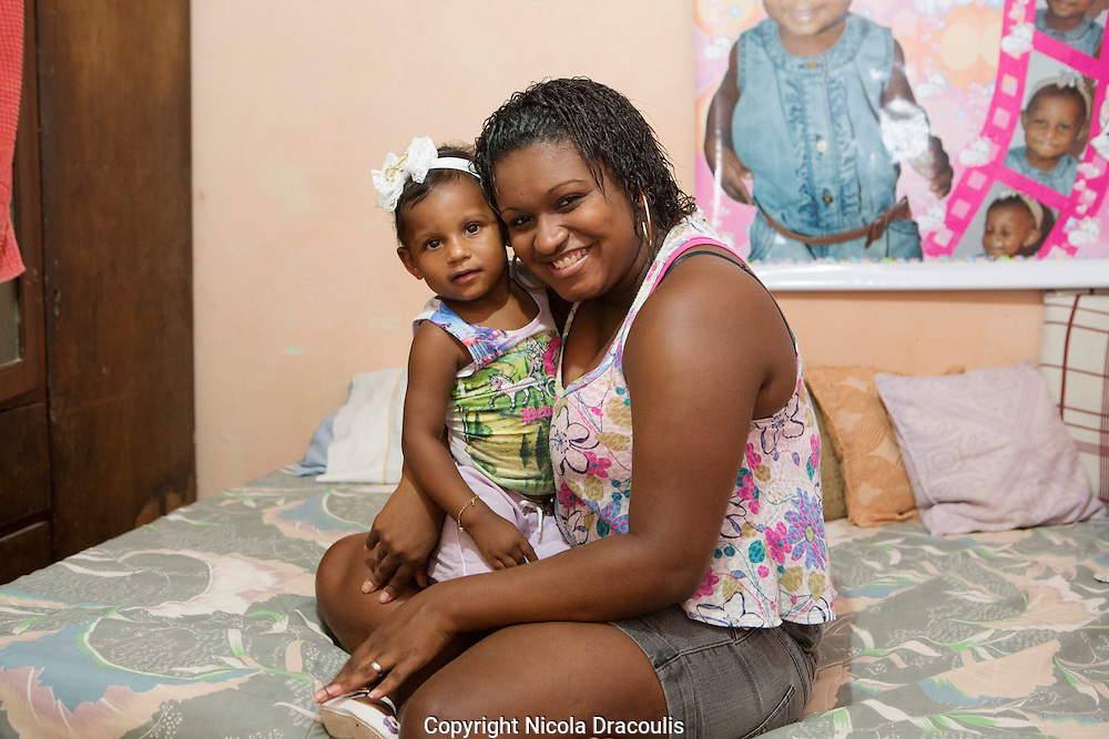 Anaderges de Jesus Souza, Vigário Geral 2013. Now 22 Anaderges was 15 years old when I first met her she works as a manicurist and is the proud mother of two year old Jamilly. They live in the same house in Vigario Geral as when I met her back in 2006 14 family members sleep here in a tiny four room house. The house is falling apart and desperately need attention. Anaderges parents are struggling to make improvements due to lack of money and currently neither can work due to health issues. They have a pile of materials to do the work but no money to complete it. Part of the series Viver no Meio do Barulho (Living in the Middle of the Noise)