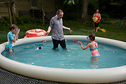 """After arriving home from work at at Sturm, Ruger & Co., where he works on the IT help desk, Dan Rothbart plays with his daughters Morgan, 8, left, and Kairi, 5, right, as his wife Jessica gathers up toys before a coming rain in Newport, N.H., Wednesday, June 30, 2021. Dan Rothbart, served in the Navy and worked on a submarine, said whenever he learns of new tax credits he brings it up with people so they are able to take advantage of the benefit. """"I stopped feeling bad about trying to maximize my returns because the rich do it,"""" he said. (Valley News - James M. Patterson) Copyright Valley News. May not be reprinted or used online without permission. Send requests to permission@vnews.com."""