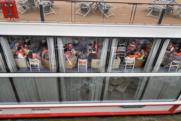 Nederland, Nijmegen, 29-7-2018Passagiersboot van een rijncruisevetrekt van de Waalkade richting Duitsland opde Waal, Rijn. Passagiers zitten in de lounge met zwemvest aan omdat er een oefening wordt gehouden.. Foto: Flip Franssen