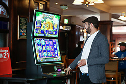© Licensed to London News Pictures. 04/07/2020. London, UK. A man at a games vending machine at THE TOLL GATE, a Wetherspoon pub in north London which reopened on Super Saturday. Cafes, restaurants, pubs and hairdressers across the UK closed on 23 March following the coronavirus lockdown. As restrictions are eased, cafes, restaurants, pubs and hairdressers reopens today. Photo credit: Dinendra Haria/LNP