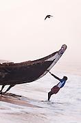 Fishermen launching their boat at Poovar Beach, near Trivandrum (Thiruvananthapuram), Kerala, India