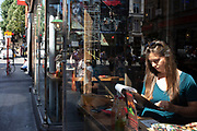 Young woman reading the menu while sitting in the window of a Chinese restaurant in Chinatown in Soho, London, United Kingdom. The present Chinatown is in the Soho area occupying the area in and around Gerrard Street. It contains a number of Chinese restaurants, bakeries, supermarkets, souvenir shops, and other Chinese-run businesses and is in itself a major tourist destination.