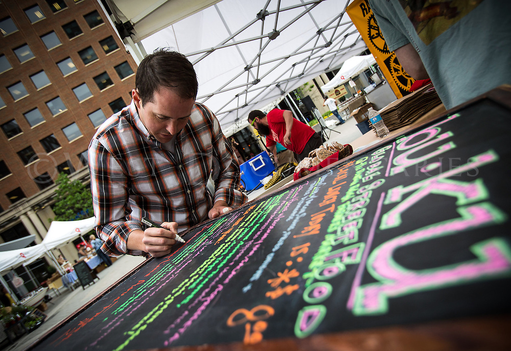 """Sean Degnan, owner of bu•ku Global Street Food, designs a placard menu for his vendor stand at the Raleigh Downtown Farmers Market on May 7. The name """"bu•ku"""" itself is an international slang twist on the phrase, """"Merci, beaucoup"""" meaning, """"Thank you very much."""" The farmers market is located along Fayetteville Street in front of City Plaza and showcases locally grown, sustainable produce and artisan food."""