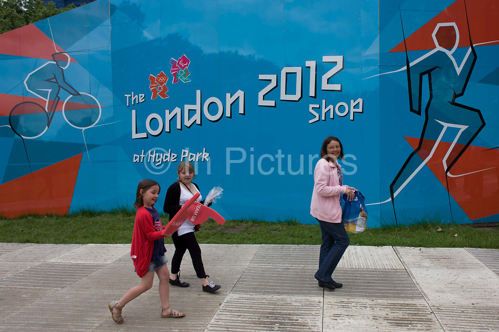 Young girls enjoy their latest purchase of foam hands as they exit the official London 2012 merchandise shop - hours before another successful gold medal win, this time by Team GB triathlete Alistair Brownlee in the men's Triathlon during the London 2012 Olympic Games. The mid-week event surprisingly drew huge crowds into the capital's largest public (royal) park for an event, not usually attracting families with children who all enjoyed the fine weather and easy temperatures. A London 2012 merchandise shop was set up on the southern side and parents and kids used the exterior hoarding featuring iconic London landmarks such as Nelson's Column, St Paul's Cathedral and Tower Bridge, to relax against after an early start from homes around the country