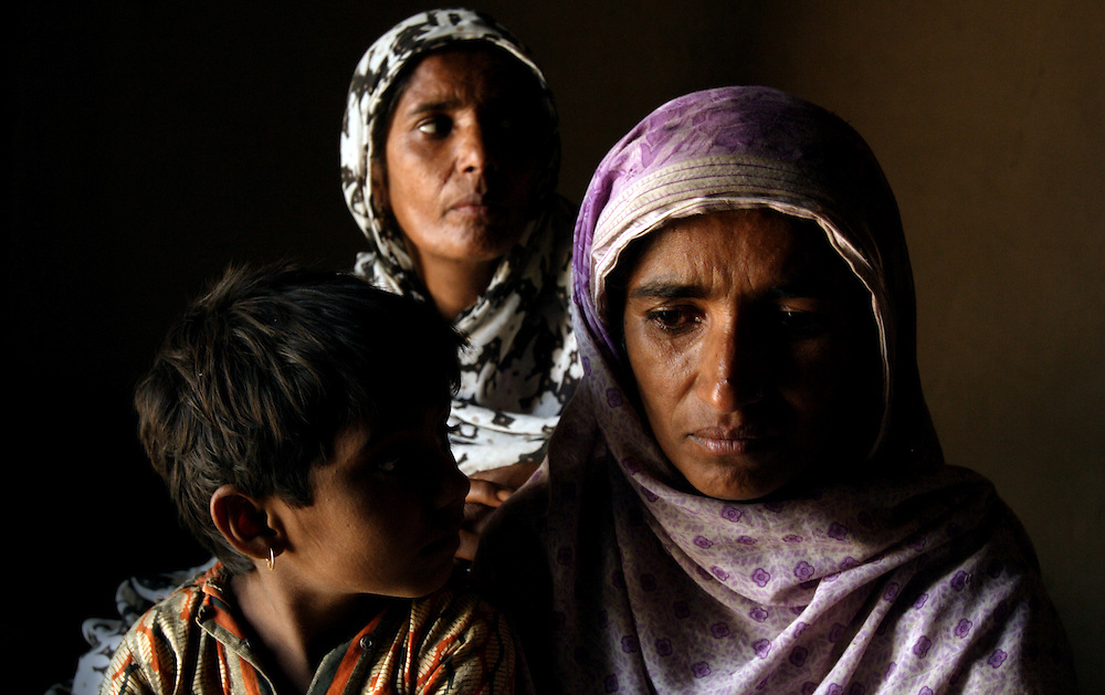 """Sisters, left to right, Zubada and Tasleem, holding daughter Rafiabibi, 6, Dera, Pakistan, April 26, 2004. They talk about their horrible experience of being gang raped by neighbors who felt they were dishonored by Zubada's son Naeem. Members of the Human Rights Commission in Multan, including social worker Asia Perveen, are working with the women to get them legal representation so they can fight the accusers in court. """"I want them to be punished,"""" said Tasleem. """"They are our enemies, I will be afraid until they are hanged publicly."""" Until now, the accused rapists are still at large."""