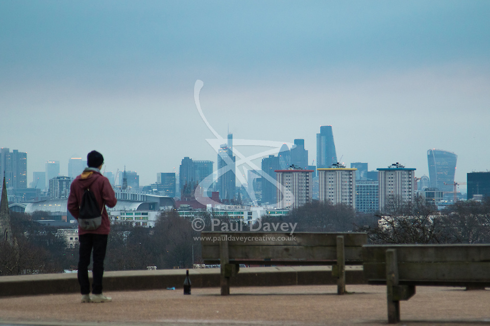 Primrose Hill, London, February 15th 2015. A walker takes in the view of London's skyline on a chilly early morning on Primrose Hill, overlooking London's skyline.<br /> ///FOR LICENCING CONTACT: paul@pauldaveycreative.co.uk TEL:+44 (0) 7966 016 296 or +44 (0) 20 8969 6875. ©2015 Paul R Davey. All rights reserved.
