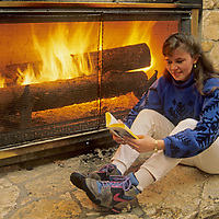 A guest at Montana's Big Sky Resort relaxes in front of a fireplace in Huntley Lodge.