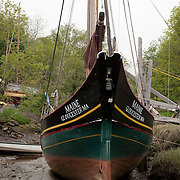 Wooden fishing boats at low tide in the Essex River, Massachusetts. Part of the Essex Shipbuilding Museum which pays tribute to the 300 year tradition of shipbuilding in this region of Massachusetts