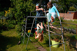 three young girls playing on the climbing frame together