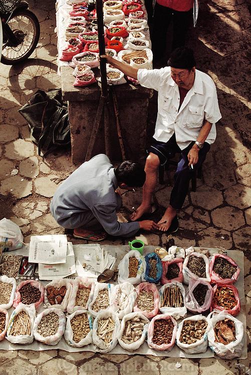 "Menghan Sunday market. A ""Barefoot"" Doctor using herbal healing in Xishaungbanna, China."