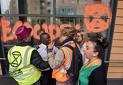 October 8, 2018 - Bristol, Bristol, UK - Bristol, UK. Activists use chalk spray to write on the windows of Bristol Magistrates Court during the 'Extinction Rebellion' campaign event 'Make Ecocide Law' about the threat of climate change, at Bristol Magistrates Court and Marlborough Street. The campaign wants to make ecocide a crime in UK law, saying the threat of climate change threatens the lives of millions of people on the planet. The campaign is organised by Rising Up, and the event happened on the day that the Intergovernmental Panel on Climate Change (IPCC) has issued a special report on the impact of global warming of 1.5C. Campaigners used removable chalk spray to write on the windows of Bristol Magistrates Court, and blocked the main road before being removed by police. There were three arrests. Rising Up plans more actions in November. (Credit Image: © Simon Chapman/London News Pictures via ZUMA Wire)