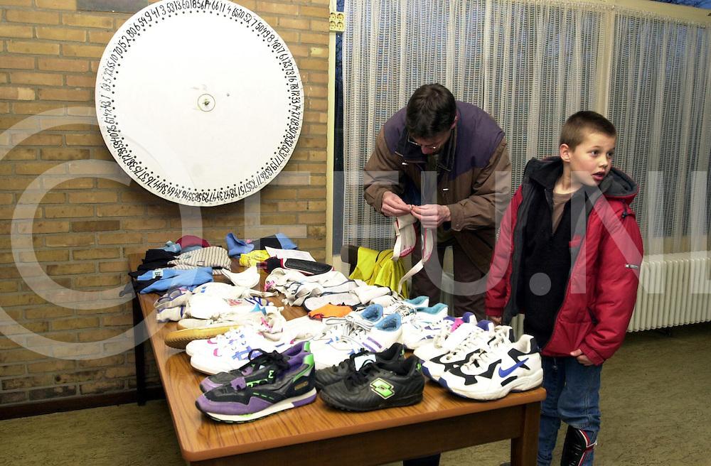 fotografie frank uijlenbroek©2001 frank uijlenbroek.010315 ommen ned.Voetbalbeurs bij OZC..Vader en zoon aan het snuffelen tussen de schoenen.