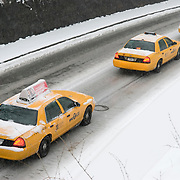 Three Taxis Driving Through Central Park, NYC During a Snowstorm