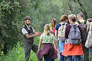 Nederland, Kekerdom, 3-6-2017Beversafari met kano in de Millingerwaard. Ranger, boswachter, Thijmen van Heerde legt aan een groep deelnemers uit wat er in het gebied allemaal te zien is. Staatsbosbeheer maakt tochten per kano  zodat belangstellenden de natuur in de Millengerwaard echt kunnen beleven. Doel is om bevers te spottenOm het water dat via Lobith binnenkomt goed te verdelen over het Pannerdensch Kanaal en de Waal én om de waterstand te laten dalen in tijden van hoog water, is de Millingerwaard verruimd voor een betere waterveiligheid. Er is een geulenpatroon gegraven bestaande uit kwelgeulen en een grote stroombaangeul. Ruimte voor de rivier de Waal.Foto: Flip Franssen