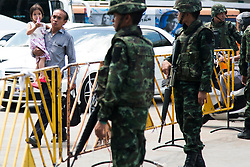 © Licensed to London News Pictures. 23/05/2014. A father and daughter walk past Thai Army soldiers in Bangkok. Thailand's army said on May 23 that 155 prominent figures, including Yingluck and ousted government leaders, were banned from leaving the country without permission following a military coup.  Photo credit : Asanka Brendon Ratnayake/LNP