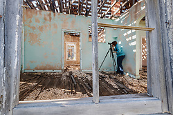 Photographer and painted house, Koehler Coal Mining Town, Vermejo Park Ranch, New Mexico, USA.