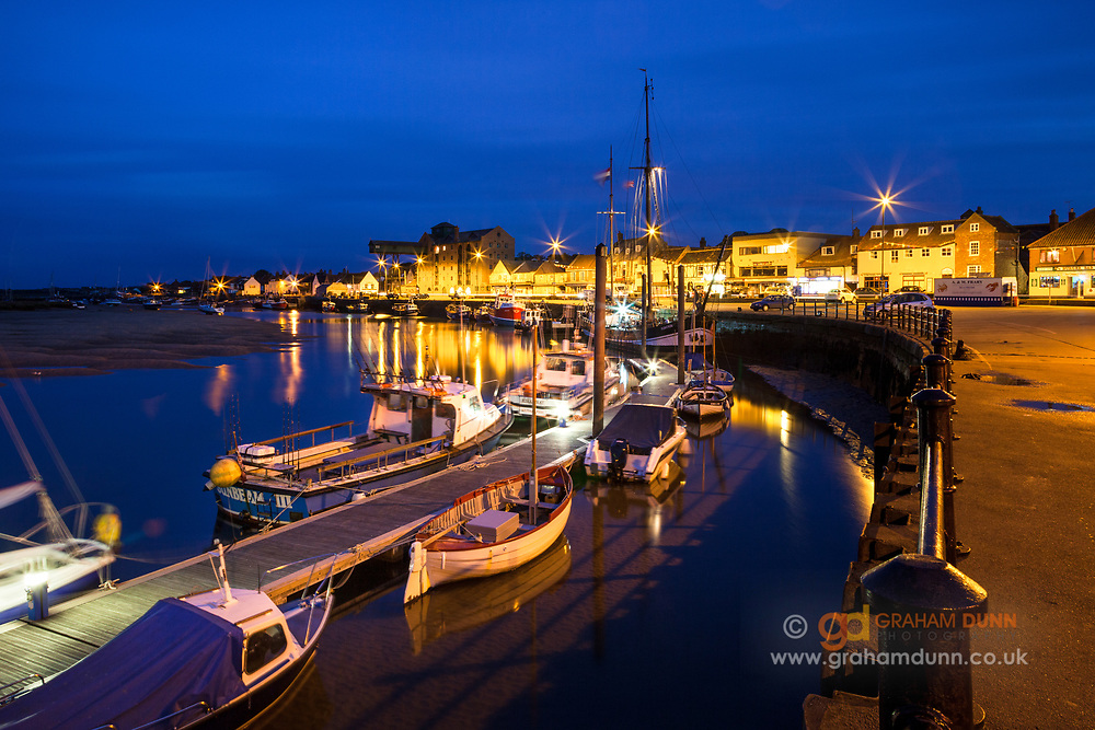 An evening view of Wells quay & harbour, North Norfolk. East Anglia. The boats and jetty curve beautifully towards the main harbour buildings. A night-time urban landscape in East Anglia, England, UK.