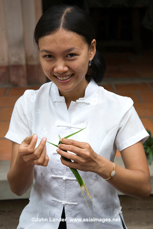 Young Vietnamese woman making an origami crane, with that stunning Vietnamese smile.  The Vietnam Delta region is famous not only for its abundant produce, labyrinth of canals and riverine activity, but the warm friendliness of its people.