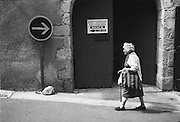 A woman walking in the street in Lasalle, a town in the Cévennes in the Gard dfepartement in the south of France.