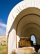 A recreated covered wagon sits in front of the Scottsbluff National Monument, Scottsbluff, Nebraska, USA.