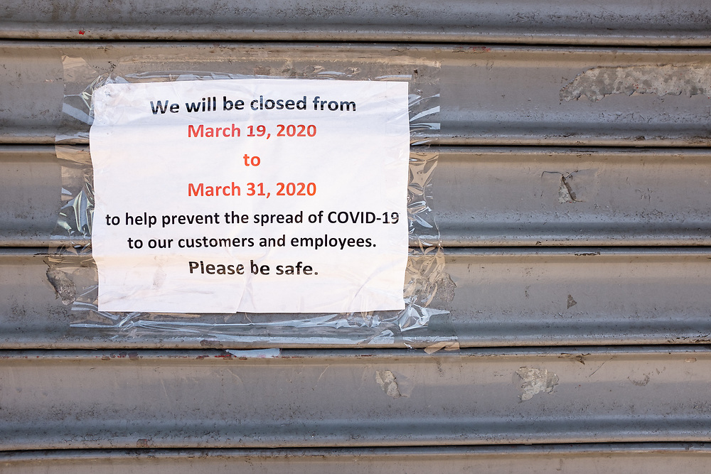 Brooklyn, NY - 26 March 2020. Residents of New York City have been asked to stay home as a result of the novel coronavirus, and all but essential businesses have been asked to close. In Brooklyn's Midwood neighborhood, many businesses have their shutters rolled down, and the few that are open limit the number of people who can enter. A sign on a closed business on Nostrand Avenue.