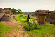 Guide Foussani Guindo walks through the rocky formations in the Bandiagara Escarpment. The Dogon Country is the most visited part of Mali with tourists visiting its tipical  villages that can be located on the cliff, on the sandy plain or in the rocky plateau