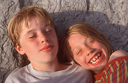 Brother and sister lying on rocks; sunbathing and laughing,