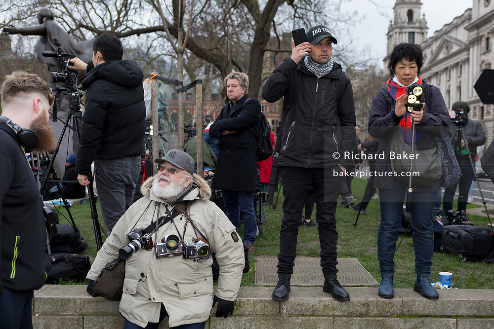 A man with a white beard has three vintage Nikon film cameras around his neck, rests on a low wall in Parliament Square next to others using mobile phones to photograph the events of Brexit Day, the date when the UK leaves the European Union, on 31st January 2020, in London, England.