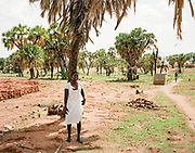 """NUBA MOUNTAINS, SUDAN – JUNE 9, 2018: A young Nuba woman in Kororak. <br /> <br /> In 2011, the government of Sudan expelled all humanitarian groups from the country's Nuba Mountains. Since then, the Antonov aircraft has terrorized the Nuba people, dropping more than 4,080 bombs on hospitals, schools, marketplaces and churches. Today, vestiges of the Antonov riddle the landscapes of daily life, where more than 1 million Nuba live in famine conditions – quietly enduring the humanitarian blockade intended to drive them out of the region. The skies are mostly clear. Yet the collective memory of the bombings remains an open wound, and the Antonov itself a persistent threat. So frequent were the attacks that the Nuba nicknamed the high flying aircraft and its dismal hum: """"Gafal-nia ja,"""" they would declare, running to the hillsides. """"The loss of appetite has come."""""""
