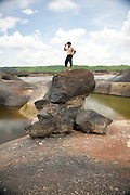 A Llanero plainsman takes in the view from atop of a volcanic boulder field in the the middle of the Orinoco River - Orinoco River Basin - Venezuela - South America