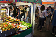 Food stalls inside at Brick Lane Market, London, UK. Foods from all over the World are available here at this popular reason to come to the area.