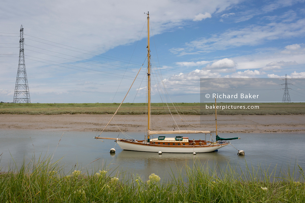 An anchored yacht and electricity pylons landscape on the Saxon Shore Way on Faversham Creek near Hollowshore, on 29th May 2019, near Faversham, Kent, England.
