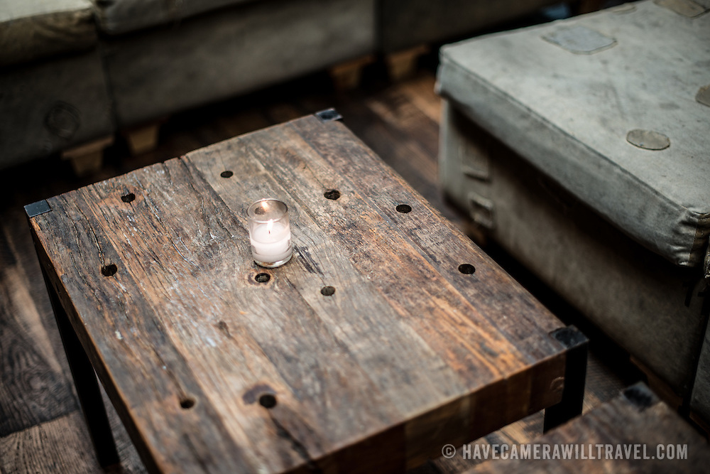 A small votive candle ssits on a rustic wooden table in a restaurant bar.