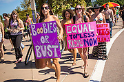 26 MARCH 2012 - PHOENIX, AZ:  MEGAN ERBE, left, and JENNA DUFFY lead a march of topless women and men in Phoenix. About 40 people marched through central Phoenix Sunday to call for a constitutional amendment to give women the same right to go shirtless in public that men have. The Phoenix demonstration was a part of a national Topless Day of Protest. Phoenix prohibits women from going topless in public so protesters, women and men, covered their nipples and areolas with tape. The men did it to show solidarity with the women marchers.   PHOTO BY JACK KURTZ