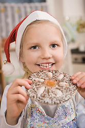 Girl eating gingerbread cookie, smiling, portrait