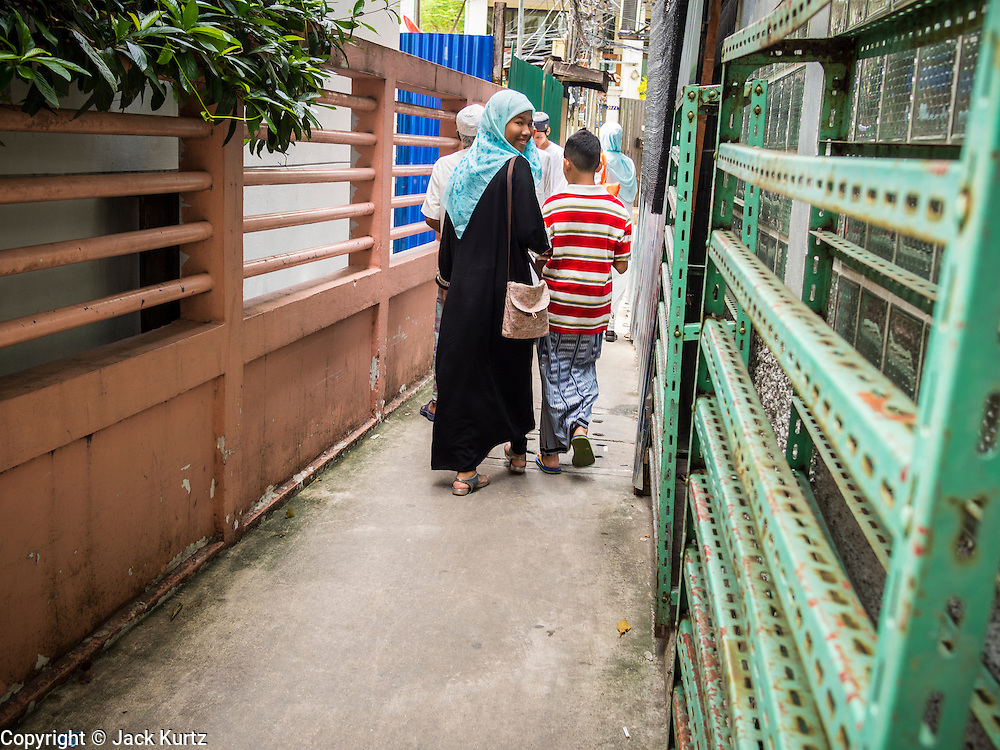 """08 AUGUST 2013 - BANGKOK, THAILAND: A family walks down an alley next to Haroon Mosque in Bangkok after Eid al-Fitr services. Eid al-Fitr is the """"festival of breaking of the fast,"""" it's also called the Lesser Eid. It's an important religious holiday celebrated by Muslims worldwide that marks the end of Ramadan, the Islamic holy month of fasting. The religious Eid is a single day and Muslims are not permitted to fast that day. The holiday celebrates the conclusion of the 29 or 30 days of dawn-to-sunset fasting during the entire month of Ramadan. This is a day when Muslims around the world show a common goal of unity. The date for the start of any lunar Hijri month varies based on the observation of new moon by local religious authorities, so the exact day of celebration varies by locality.      PHOTO BY JACK KURTZ"""