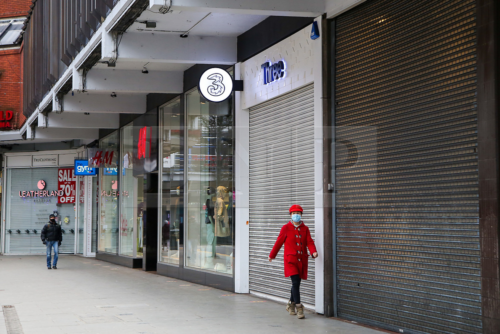 © Licensed to London News Pictures. 19/02/2021. London, UK. A woman wearing a face covering walks past closed retail businesses in Wood Green, north London. According to the Office for National Statistics (ONS), in January 2021, retail sales decreased by 8.2%, compared with December 2020. Tighter nationwide coronavirus (COVID-19) restrictions on non-essential retailers which forced them to close led to the drop in January's retail sales. Departmental and clothing store sales were particularly affected. Photo credit: Dinendra Haria/LNP