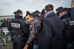 October 24, 2016 - Calais, France - Some tension at the entrance of the warehouse where many migrants want to go inside to take the bus in Calais, France, on 24 October 2016. One third of the migrants living in the Jungle was today registered and dispatched vias various regions of the French territory. They were asked to queue in front of a warehouse where they were given a bracelet with a specific colour. They eventually got into their allocated bus. (Credit Image: © Guillaume Pinon/NurPhoto via ZUMA Press)