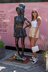 © Licensed to London News Pictures. 23/07/2021. LONDON, UK.  A woman stands with the statue of Amy Winehouse by sculptor Scott Eaton in Stables Market in Camden Town on the tenth anniversary of the late singer's death.  Photo credit: Stephen Chung/LNP