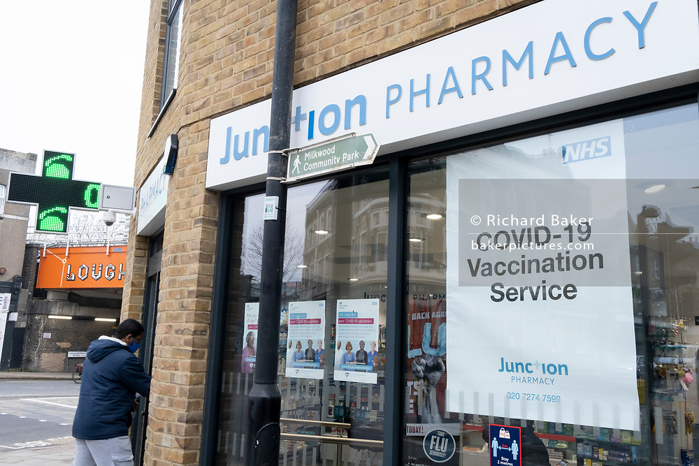 A youth enters a south London Pharmacy which is performing pre-arranged Covid-19 vaccinations during the third lockdown of the Coronavirus pandemic, on 2nd March 2021, in London, England.