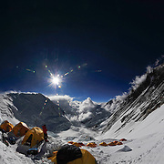 A climber stands outside his tent at sunset at 24,000 foot Camp 3 on Mount Everest's Southeast Ridge, Nepal.<br /> <br /> To see the fullsize interactive panorama, please visit: http://www.gigapan.com/gigapans/152790.