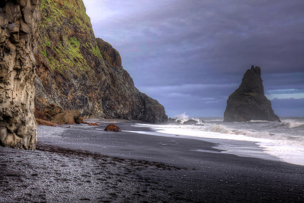 Located near Vik, Iceland, the beautiful black sand beach of Reynisfjara includes the signature formation Reynisdrangar (name for the basalt sea stacks partly seen in the water).