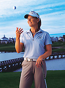 Female professional golfer Annika Sorenstam tosses a ball into the air while posing on a golf course