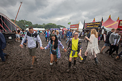 © Licensed to London News Pictures . 07/06/2014 . Heaton Park , Manchester , UK . People traipse through the mud at the festival .  Parklife music festival in Heaton Park Manchester following heavy overnight rain . Photo credit : Joel Goodman/LNP