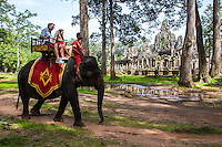 Elephant Rides at Bayon, a richly decorated Khmer temple at Angkor Archeological park in Siem Reap, Cambodia.  Built in the late 12th century as the official state temple of the Buddhist King Jayavarman VII, the Bayon stands at the centre of Jayavarman's capital, Angkor Thom.