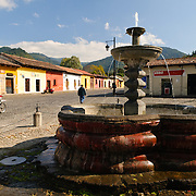 A Spanish colonial fountain on a cobblestone street in Antigua, Guatemala.